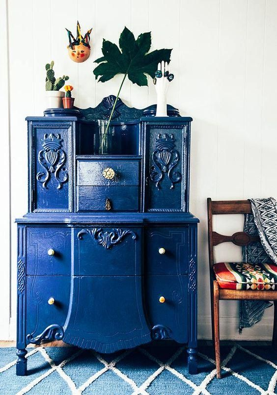 Vintage thrifted dresser painted a glossy deep cobalt blue decorated with bohemian accents, accessories and textiles draped on a Mexican fabric upholstered accent chair.