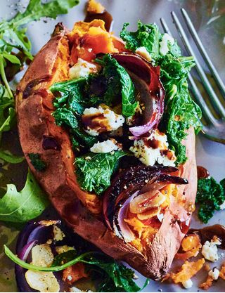 This easy, hassle-free midweek main sees sweet potatoes stuffed with crunchy kale, fragrant spices and creamy feta before being baked until the jackets crisp deliciously up.