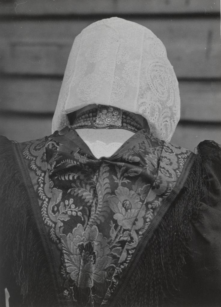 Mevrouw Van den Brink in streekdracht uit Eemnes.  Ze draagt de zondagse kerkdracht met 'vierkante muts'. Onder deze kanten muts een ondermuts en een zilveren oorijzer met aan de uiteinden gouden 'tuten' en gouden steekspelden. Verder een zwart Tibet jak, rok en schort. Over het jak een zwart zijden overdoek met ingeweven bloempatronen in donker paars-rose en zwart garen franje. Om de hals een halssnoer met sluiting in de nek. 1952 #Eemnes #Eemland #Utrecht #vierkant