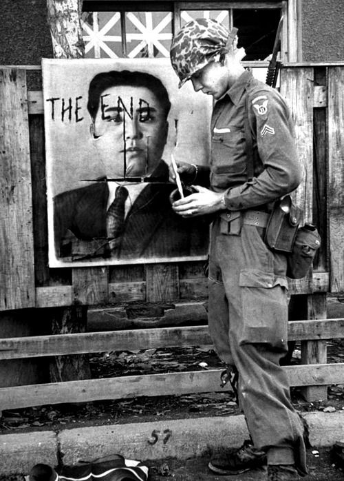 A paratrooper paints the end to the Red Premier. North Korea, 1950.  Howard Sochure