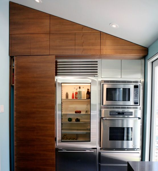 A great space-saving idea in a renovated Victorian flat in San Francisco by Abueg Morris Architects is an appliance wall. The refrigerator, freezer, oven, microwave and washer/dryer are artfully arranged to fit in a compact 8-foot-wide space. Storage cupboards sit above using every inch of the wall.