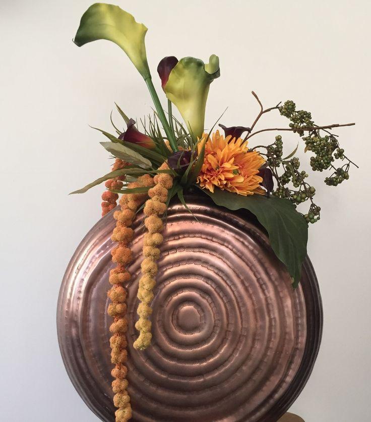 Een najaarscreatie opgemaakt met verschillende zijden bloemen. Oranje chrysant, verschillende calla's
