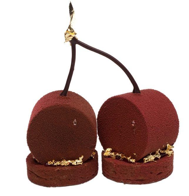 Ladurée. Les cerises, habillées d'une fine feuille de chocolat noir recouvert d'un velours de chocolat noir aux reflets acajou, sont délicatement posées sur un biscuit au chocolat amer décoré de feuilles d'or.
