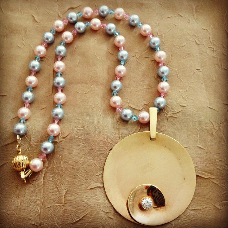 Colar com pérolas swaroviski rosas e azuis com pingente em prata com banho de ouro rosa e zircones no centro.