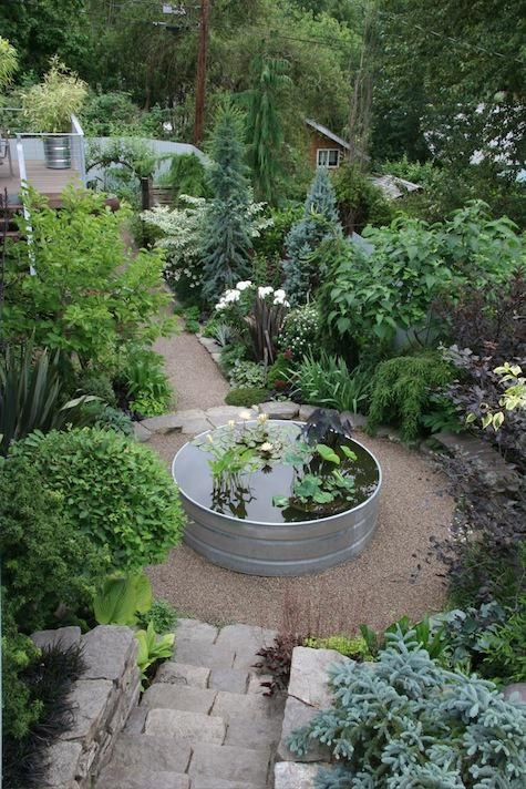 A galvanized stock tank provides a focal point on a circular pea gravel path terrace
