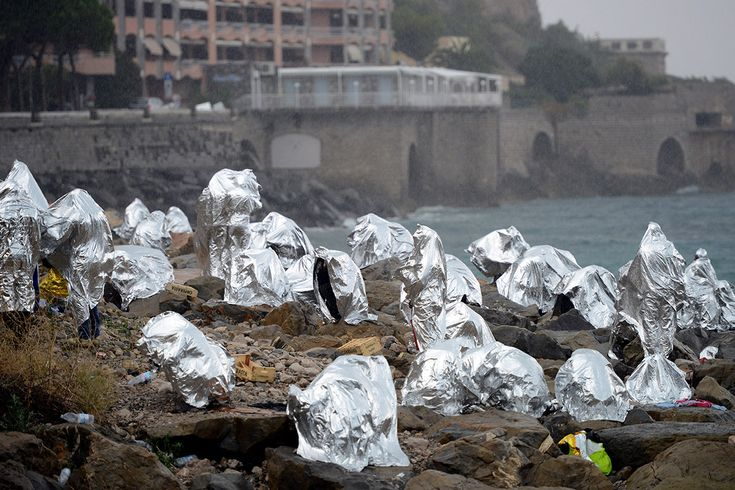 A group of migrants wrapped in thermal blankets huddle on the seawall between Ventimiglia in Italy and Menton in France, June 14, 2015. (Eric Gaillard/Reuters)