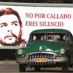 """Un """"almendrón"""" cubano, vehículo fabricado antes de 1960, pasa por un mural alusivo al héroe revolucionario Ernesto """"Che"""" Guevara en La Habana."""