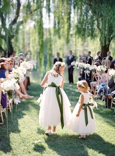 Sweet flower girls with matching green sashes: http://www.stylemepretty.com/2015/11/12/summer-willow-tree-wedding-at-black-swan-lake/ | Photography: Jose Villa - http://josevilla.com/