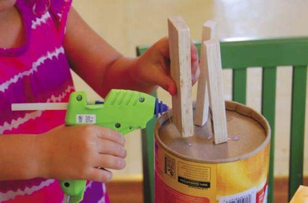 Сядьте рядом с ребенком и покажите ему, как соединять предметы с помощью клеевого пистолета, скотча, степлера и клея.