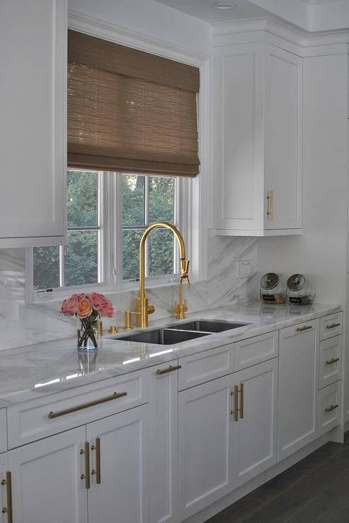 white cabinets and positioned above a stainless steel dual sink accented with a brass gooseneck faucet mounted to a marble countertop a white