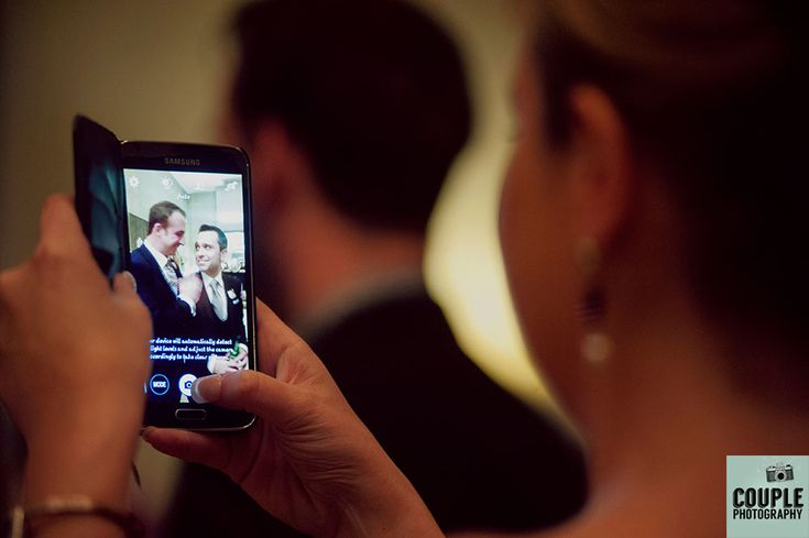 Guests take photos of the groom on their phones. Wedding at Castle Dargan Hotel Photographed by Couple Photography. Ireland.