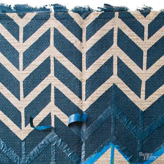 When it comes to trending prints and patterns, geometric shapes have taken center stage. The interior design detail can carry a hefty price when featured on store-bought rugs, so consider re-creating your favorite geometric print with a few common crafts tools. Take a basic flat-weave or sisal rug from ordinary to extraordinary with painters tape and your choice of interior wall paint. Tape off your design, apply paint, and let dry before revealing your masterpiece!/