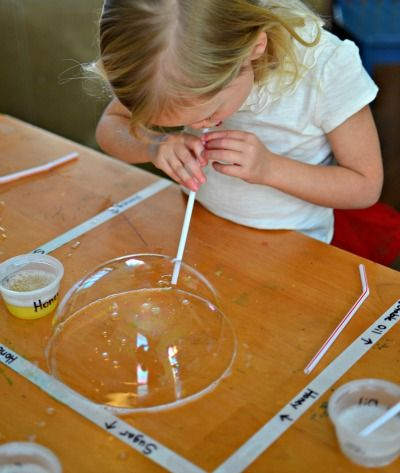 All we had to do was mix together ¼ cup dishwashing liquid and 1 cup water in a bowl to create a bubble solution. Next we dipped a cloth into the bowl and wiped it across a table. The kids then dipped the end of their straws into the bubble solution, put the end of the straw onto the wet table, and blew gently. Bubbles! And then not just bubbles, but BIG bubbles, followed by really ENORMOUS bubbles