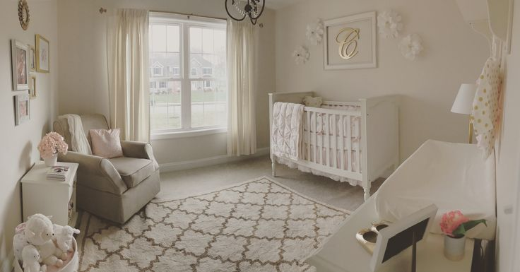 Neutral white, gold, and blush pink nursery. Crepe paper wall flowers. Stuffed animals. Baby girl. White basket. Pink pillow. White throw blanket. Pottery barn crib. Bright nursery. Monogram. Pink flowers. Hydrangeas. Beige rocker. Glider. Rocking chair. Framed initials. Trefoil rug. Gold chandelier. White curtains. White changing table. White changing pad.