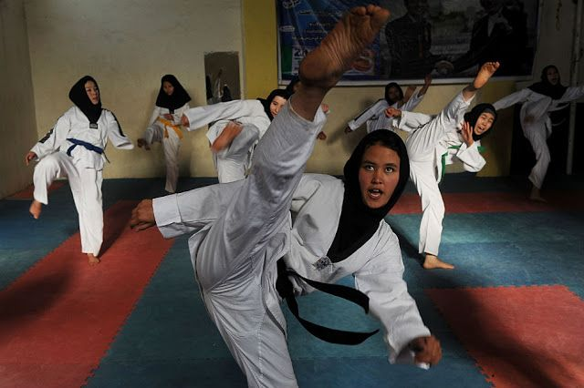 Afghan girls practice Taekwondo moves during a martial arts class in Herat in January 2013. Mauricio Lima/AFP/Getty Images.