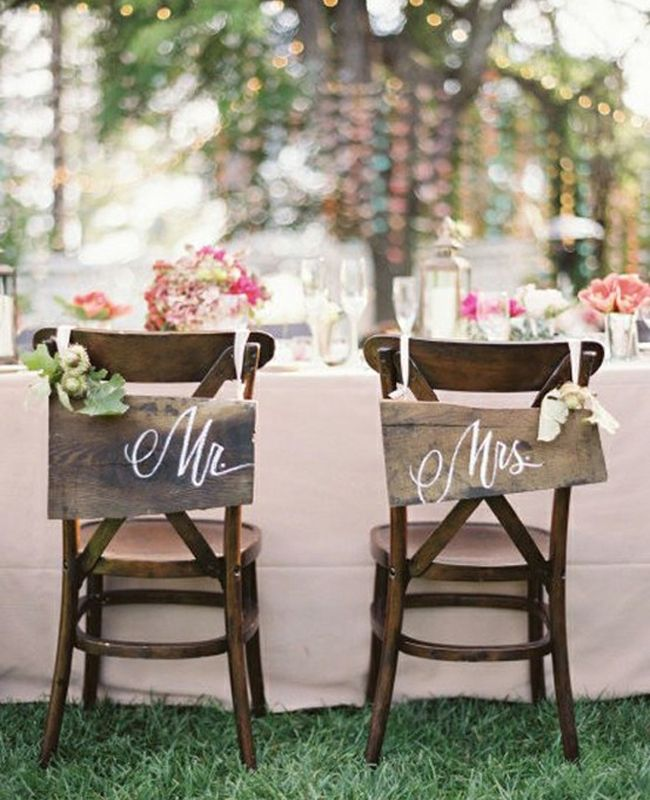 Rustic wood signs hang from the backs of these wedding chairs.