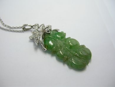 One carved jade pendant set in 14 karat white gold. Fifteen single cut diamonds (0.45 carats: I1-2 clarity: G-H colour). One jadeite jade depicting a cluster of fruit, natural greyish to brownish green in colour.