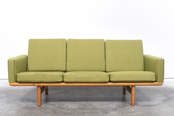 Three seat sofa in oak and designed by Hans J. Wegner for Getama in 1955. Sofa features sprung cushions with grass green wool covers.