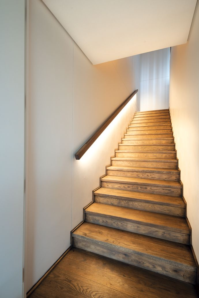 The staircase and the upstairs flooring is oiled oak. LED lighting under the handrail gives off a soft light. http://amzn.to/2sb1KKv