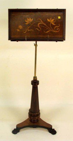WALNUT MUSIC STAND:  Early 20th century. A brass and inlaid walnut music stand on a tapering column walnut tripod pedestal ending in carved paw feet.