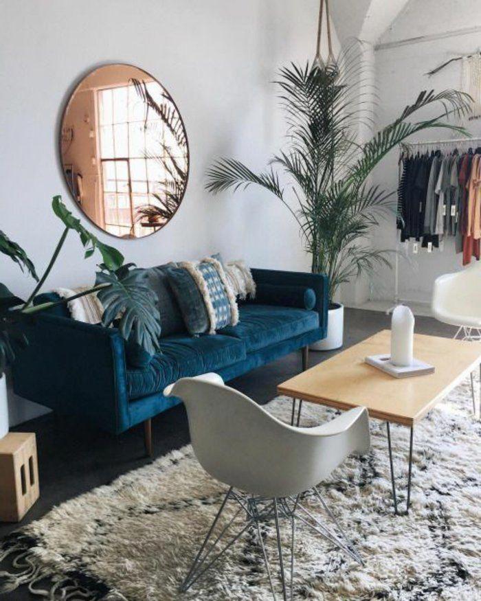 deco salon bleu canard, grand salon avec les murs gris, un sofa bleu, miroir mural rond et tapis ...