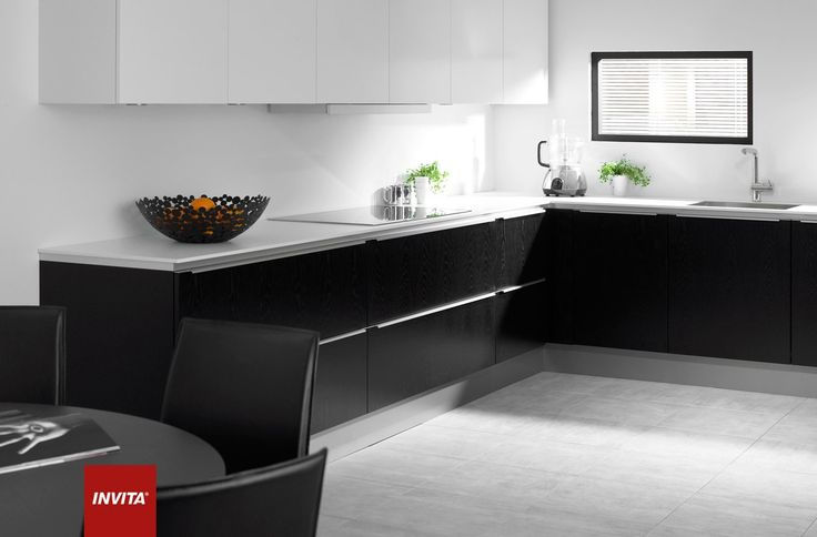 """Det minimalistiske udtryk brydes af runde lamper og et ditto spisebord med tilhørende læderstole. De mange skuffer markeres af Steelline-grebet, som er nemt at få fat i. Bordpladen er af laminat og svæver over elementerne takket være en underliggende plade. Athena Steelline i sortbejdset eg med hvide Athena overskabe. """"Svævende"""" bordplade i 40 mm hvid kompaktlaminat. Underlimet vask og vandhane fra Blanco. Hvidevarer fra Siemens. Lyshylder fra Invita. Lamper fra Lampefeber (model Pearl)."""