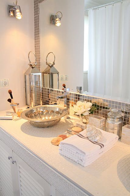 Bathroom with metallic tile around the mirror, vessel sink, mercury glass accents