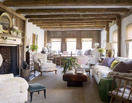 In the living room of this 18th-century Long Island farmhouse, designer Tom Scheerer grouped his clients' heirloom antiques with newer pieces for a relaxed conversation between styles. The hearthside gathering, on a sea-grass rug from Design Materials, mixes Louis XV armchairs, a Luther Quintana sofa, and one of a pair of thrift-shop wing chairs in Shawnama Crewel from Travers. The faux-tortoiseshell coffee table is a vintage Karl Springer piece.   - HouseBeautiful.com