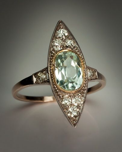 Art Deco Vintage Aquamarine and Diamond Ring Moscow, circa 1930 The marquise (navette) shaped ring with a millegrain border is centered with an oval aquamarine (approximately 1.53 ct) set in a gold milgrain bezel, flanked by six old mine and old European cut diamonds set in silver over gold.