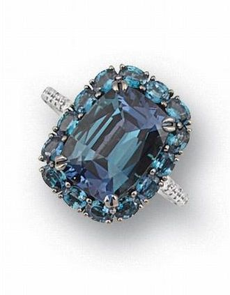 An alexandrite and diamond ring The cushion-shaped alexandrite, weighing 7.65 carats, within a four-claw setting, surrounded by oval mixed- cut alexandrites, to brilliant-cut diamond shoulders and gallery, mounted in platinum.