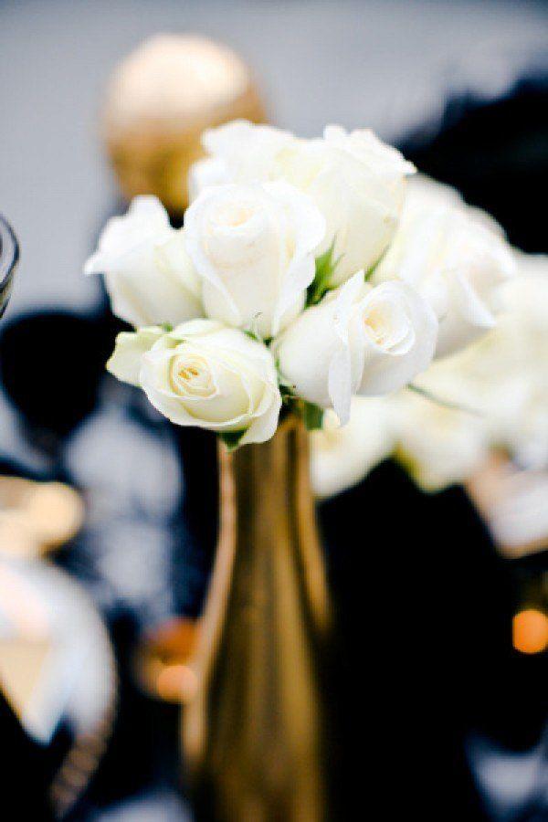 Metallic gold vase with accompanying white roses