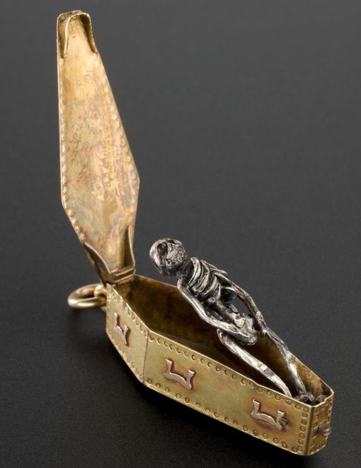 A Victorian charm in the form of a skeleton within a coffin, a symbol of death and memento mori.
