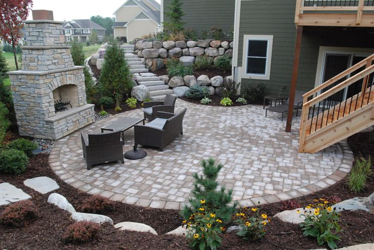 Retaining wall/stairs leading to patio below by walkout and deck stairs - Heins Nursery