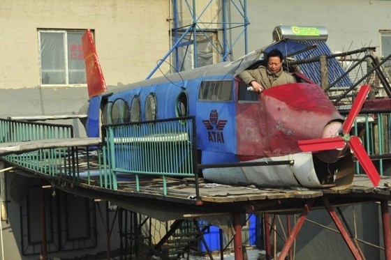 Shenyang, China. A man constructs a plane out of scrap metal.