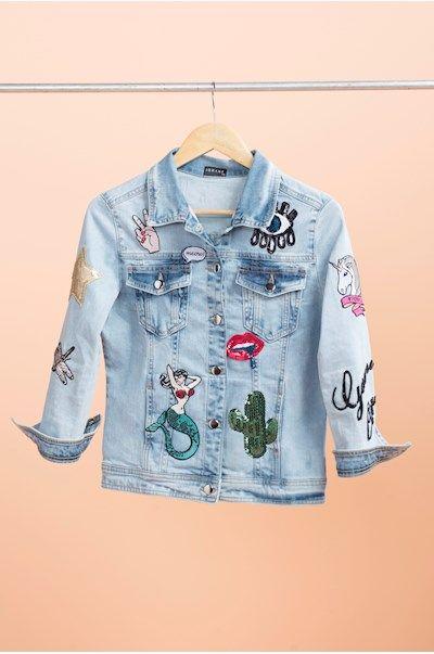 Jaqueta jeans com aplicações de patches diversos, salpicadas em toda a peça. Manga 3/4. Disponibilizamos a opção de personalização com o seu nome no verso da jaqueta, caso queira personalizá-la, sele...