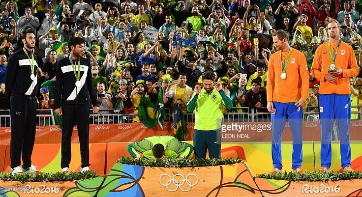 TOPSHOT - Brazil's gold medallists Alison Cerutti (C-L) and Bruno Oscar Schmidt (C-L) prepare to step on the podium at the end of the men's beach volleyball event at the Beach Volley Arena in Rio de Janeiro on August 19, 2016, during the Rio 2016 Olympic Games. / AFP / Leon NEAL