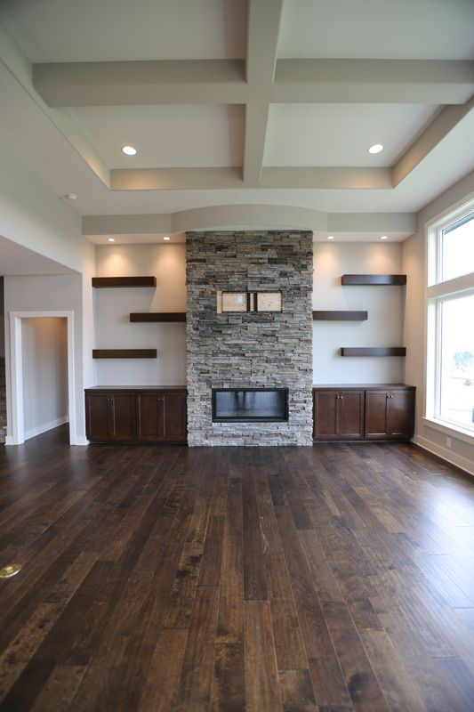 stone fireplace, gas log fireplace, floating shelves and cabinets on both sides.