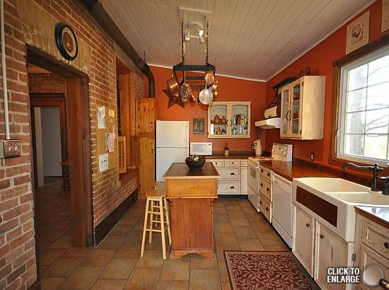 Burnt Orange Kitchen baseboard on exposed brick | kitchen/dinning room | pinterest