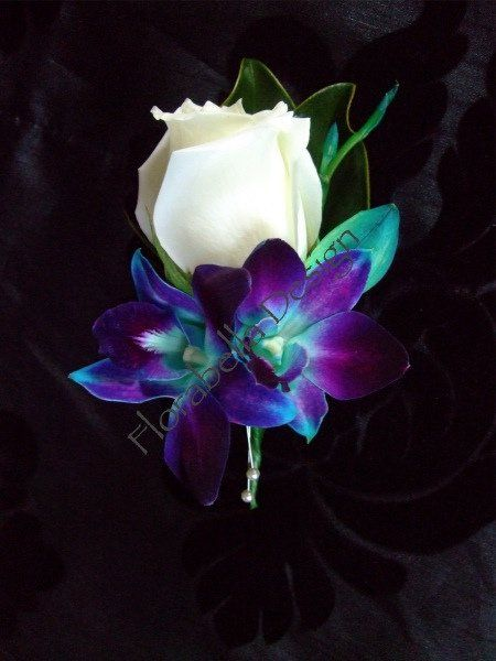No peacock feather in this boutonniere but the purple blue orchids with the white rose would look nice for a peacock color theme wedding