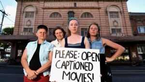 — a movie theater refuses to show open captions  The Westgarth Cinemas has refused to open caption their movies. The Deaf Community is very angry about it. A story about the theater's refusal was written up in a local newspaper. The theater has made available their individual captioning devices, but the deaf patrons said either the device is defective or is not available upon demand! The theater is in Australia. This picture is self-explanatory.