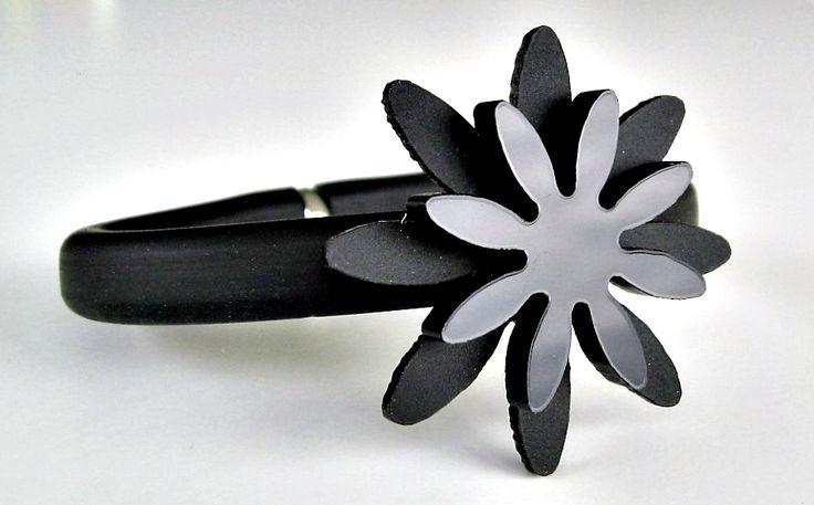 Armband av gummi med blomma i plexiglas. Bracelet made of rubber and plexiglass.