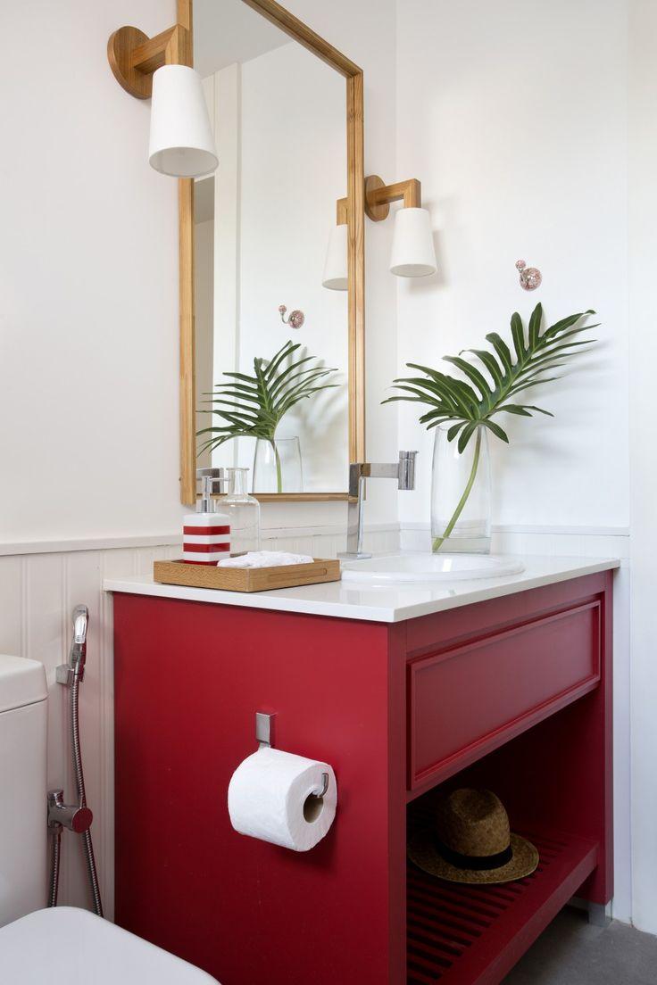 banheiro com decoração em vermelho, branco e toques de madeira