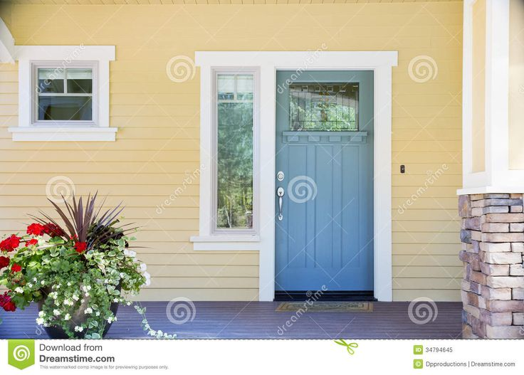 yellow siding and front door colors | front entrance of a home with a blue door, yellow siding, and a ...