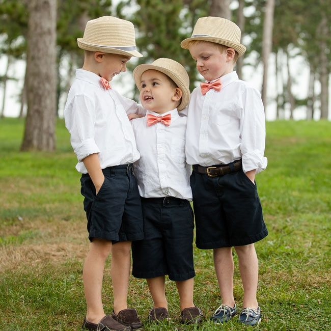 The three boys in the wedding party wore navy shorts, which button-down shirts and coral bow ties.