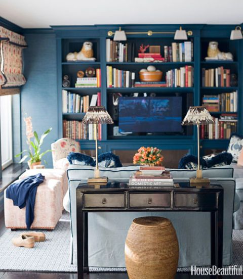 "A formal dining room was transformed into a cozy media room in this Manhattan apartment. Designer Ashley Whittaker used blue to make the room darker (better for screening movies and TV shows). ""It's very sunny, but we tamed the brightness with Prussian blue,"" she says. The shade is a half-and-half mix of Twilight (#2058-10) and Gentleman's Gray (#2062-20) by Benjamin Moore 