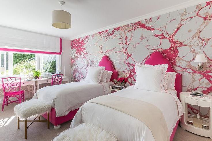 Silver and pink girls' bedroom features an accent wall clad in silver and pink paint splatter wallpaper lined with a pair of hot pink twin beds dressed in white and pink scalloped duvet & shams placed between three white mismatched nightstands.