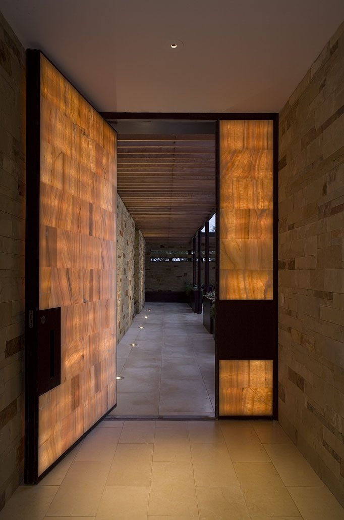Glowing onyx and steel entry door. Lake Travis Retreat by Dick Clark Architecture, in Lake Travis, Texas, US.