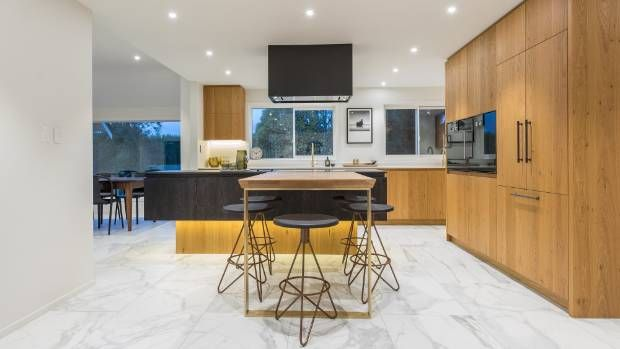 A bank of cabinetry on the right side of the kitchen includes an integrated Fisher & Paykel French Door refrigerator and ...