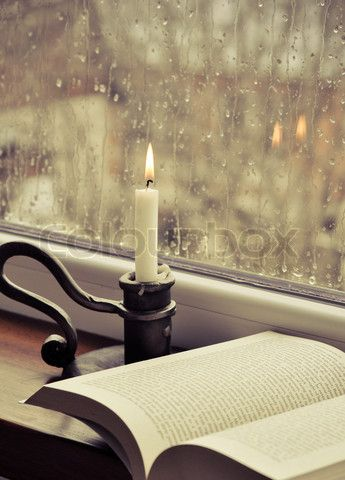 Stock image of 'A book and a candle on a rainy day'