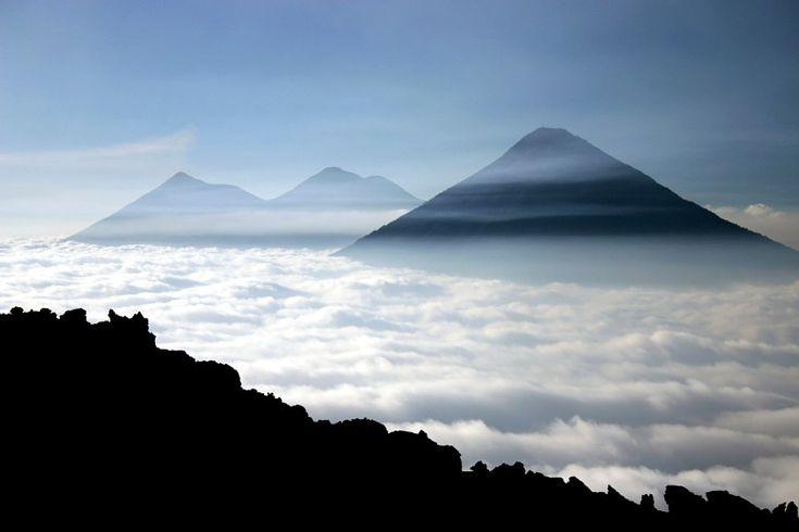 Visite Guatemala. Vista do alto da montanha Pacaya de vulcões acima de um mar de nuvens. Guatemala passeios.